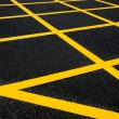 Cross yellow lines on blacktop — Stock Photo #19209191