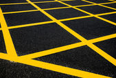 Cross yellow lines on blacktop — Stock Photo
