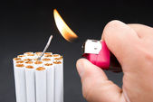 Igniting a bundle of cigarettes with tinder — Stock Photo