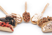 Chinese herbs on wooden spoons — Stock Photo