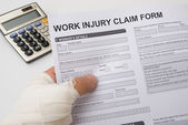 Hurted hand holding a work injury claim form — Stock Photo