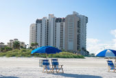 Beach with deck chair near to buildings in a sunny morning — Stock Photo