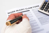 Filling up a work injury claim form — Stock Photo