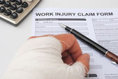 Hurted hand and work injury claim form — Stock Photo