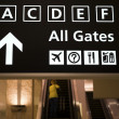 Departure gates sign and escalators — Stock Photo