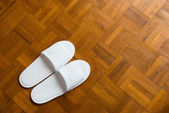 Pair of white slippers on a wooden floor — Stock Photo