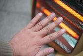Heating up a hand in front of an electric heater — Stock Photo