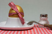 Golden egg in an egg cup on a red patterned napkin — Stock Photo