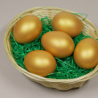 Five golden eggs in basket on green grass — Stock Photo