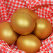 Five golden eggs in a patterned napkin — Stock Photo