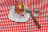Golden egg in an egg cup and spoon loop — Stock Photo
