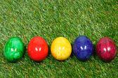 Huevos coloridos mienten en un césped sintético — Foto de Stock
