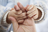 Baby two little hands hold adult hand closely — Stock Photo