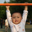 Baby play with horizontal bar — Stock Photo