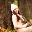 Pretty student girl with laptop in autumn park. Young European — Stock Photo