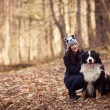 Beautiful Girl with her dog in autumn forest. Bernese Dog — Stock Photo #18519081