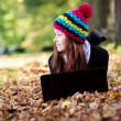 Royalty-Free Stock Photo: Beautiful young girl with laptop in autumn park. Young European