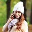 Stock Photo: Pretty young womtalking on new cell phone in autumn park