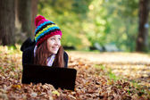Beautiful teenage girl working on laptop in park during autumn — Stock Photo
