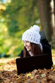 Beautiful young girl with laptop in autumn park. Young Girl — Stock Photo