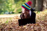 Beautiful young girl with laptop in autumn park. Young European — Stock Photo