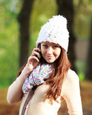 Pretty young woman talking on new cell phone in autumn park — Stock Photo