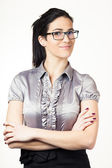 Portrait of a happy young confident business woman standing with folded hands against white background — Stock Photo