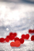Small red hearts on snow — Stock Photo