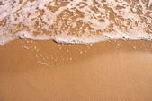 Closeup of sand and small wave — Stock Photo