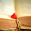 Small red heart on opened book — Stock Photo
