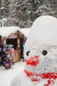 Snowman at Christmas fair with kiosk — Stock Photo