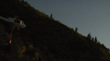 Yangın söndürme helikopteri ağır çekimde gün batımına doğru uçar — Stok video