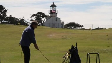 Man hits golf ball with lighthouse an American flag in distance — Stock Video