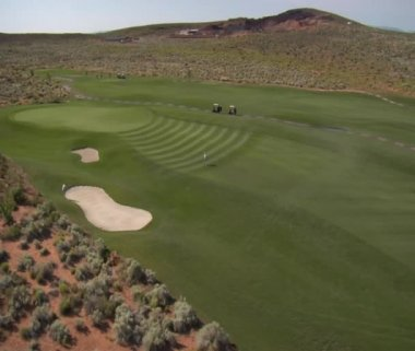 Aerial shot of golfers on desert course — Stock Video