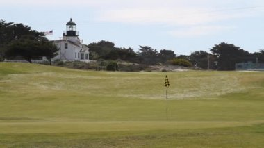 Lighthouse an American flag on golf course — Vídeo Stock