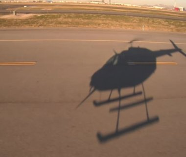 Shadow of helicopter hovering over airport runway — Stock Video