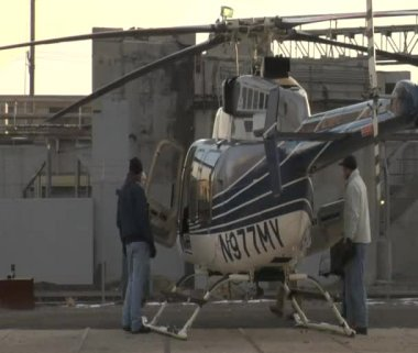 Men inspect stationary helicopter — Stock Video
