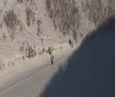 Aerial shot of skiers entering shadow — Stock Video