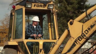 Construction worker operates backhoe — Stock Video