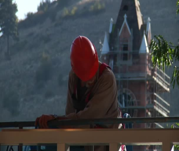 Trabajador de la construcción con casco y Torre del reloj — Vídeo de stock