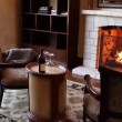 Cozy chairs in front of fireplace with bottle of wine — Stock Video #29869655