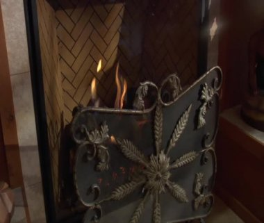Fire burning behind ornate metal screen — Stock Video