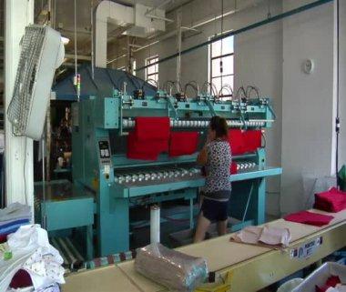 Vrouw neemt rode doek van industriële strijken machine — Stockvideo