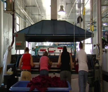 Four ladies operate industrial ironing machine — Stock Video