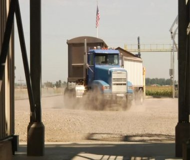 Semitruck in dirt parking lot with American flag — Stock Video