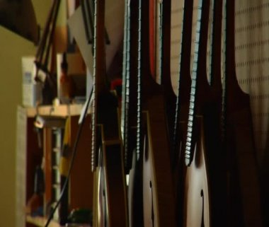 Stringed instruments and worker smoothing wood — Stock Video