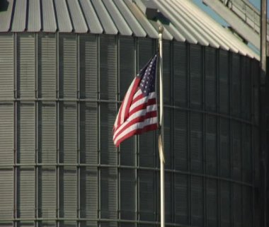 American flag waves in front of grain elevator — Stock Video