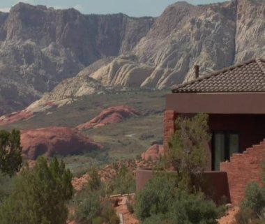 Large desert home with the red rock desert in distance — Stock Video