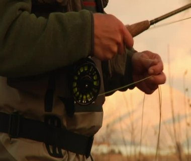 Tight shot of hand on flyfishing reel while casting — Stock Video