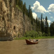Stock Video: Flyfishing driftboat near rocky cliff